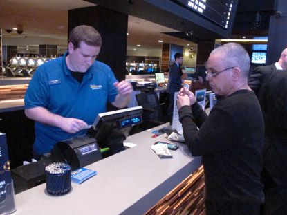 A gambler prepares to hand over cash at the sports betting window inside the Tropicana casino in Atlantic City N.J. on March 8, 2019. File. (AP Photo/Wayne Parry, File)