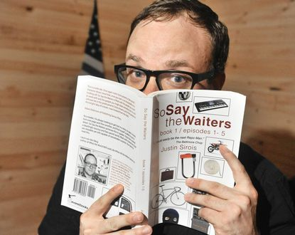"""Baltimore author Justin Sirois holds a copy of his self-published book, """"So Say the Waiters."""""""