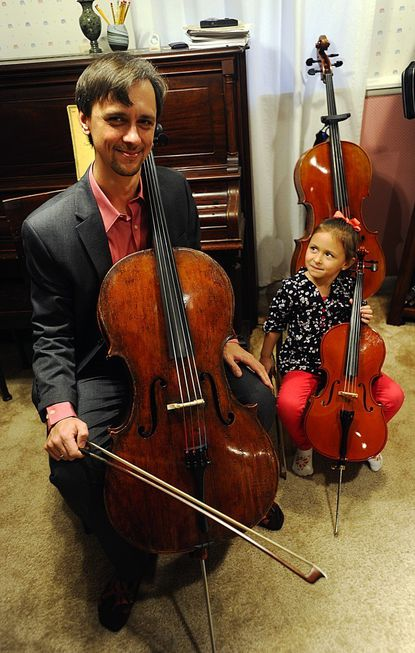 Maxim Kozlov and his daughter Sonja, 5, sit with their cellos in Kozlov's home studio in Eldersburg Jan. 30. Kozlov, originally from Russia, is a professional cello player who has performed in orchestras all over the world.