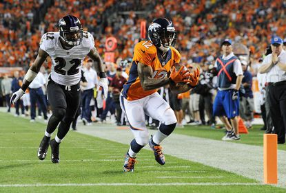 Denver Broncos wide receiver Andre Caldwell catches a 28-yard pass before running in for the touchdown in front of Ravens cornerback Jimmy Smith in the third quarter at Sports Authority Field at Mile High.