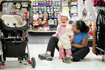 Julie Wolff, right, of Hampden smiles while her 15-month-old daughter Gabby Wolff tries on a lamb Halloween costume at Party City in Anneslie on Oct. 22.
