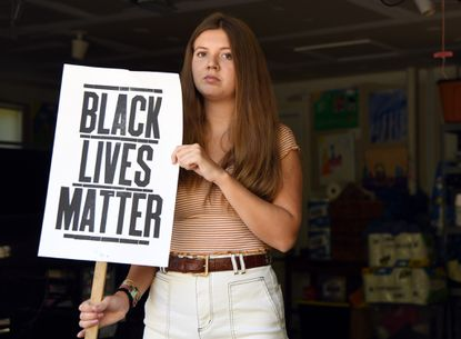 Flannery Supplee, a 2018 graduate of Hereford High School, is one of the signers of a petition which seeks to ban hate speech and hate symbols in Baltimore County Public Schools. Here, she holds one of the signs she has carried during rallies.