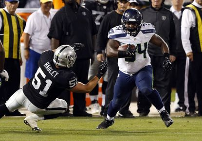 In a preseason game, fullback Kiero Small, then of the Seattle Seahawks, gains a first down against Oakland Raiders linebacker Spencer Hadley. Small was promoted to the full roster by the Cleveland Browns Monday.