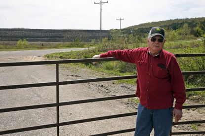 Tim Tanksley, who has been fighting for years trying to convince Oklahoma lawmakers to crack down on the coal ash dumping, stands outside a dump site in Bokoshe, Okla.
