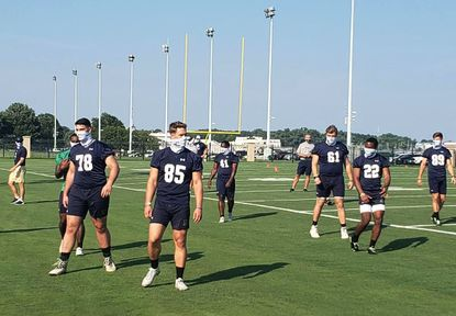 Navy football players wearing masks during a practice in late July.