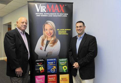 Marty Gallant, left , President/CEO of Natural Products Solutions and Travis Pendergast, Vice President of Sales, right, stand with a banner showing their company spokesperson Dr. Laura Berman.