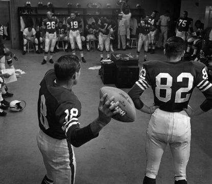Cotton Davidson (holding ball) warms up in the Colts locker room with Raymond Berry (No. 82), John Unitas (No. 19), and Royce Womble (No. 26) in 1957.
