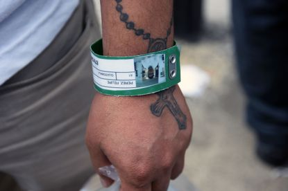 "Baltimore Mayor Bernard C. ""Jack"" Young signed an executive order Wednesday directing city agencies to protect immigrants and approved new funding for lawyers to represent residents facing deportation. In this July 31, 2019, photo, a Guatemalan migrant's identification wristband is shown upon his arrival at an air force base in Guatemala City after being deported from the United States."