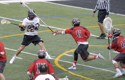 Towson attackman Ryan Drenner, left, scores against Fairfield defenseman Andrew Eidenshink, center, and goalkeeper Tyler Behring, right to give Towson a 3-2 lead in the first half of a college lacrosse game.