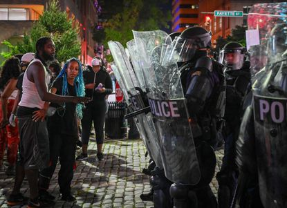 Protesters face off with police at Baltimore City Hall Saturday night in response to the police custody death of George Floyd in Minneapolis.