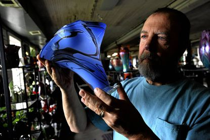 Glassblower Foster Holcombe, co-owner of glass studio Art of Fire, holds a Signature Series vase he crafted.