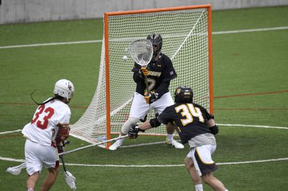 Towson's Tyler White, No. 2, stops a shot by Denver's Zach Miller during the first half of Sunday's game at Denver.