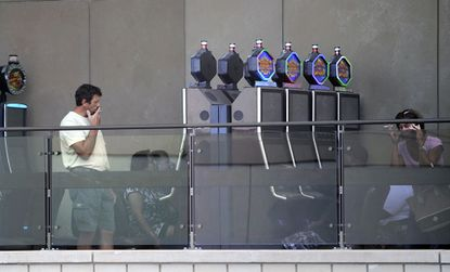 Jesse Davis, left, of Baltimore, smokes a cigarette while Jedy Stone, right, of Baltimore plays the slot machine outside on a balcony at the Horseshoe Casino designated for smokers.