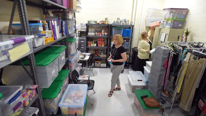 Roxann Anderson, left, a pupil personnel worker and Christine Ratych, a school nurse, navigate a pantry of donated items at Parkville High School. The school is part of the Student Support Network, a nonprofit helping students and their families with food and other needs.