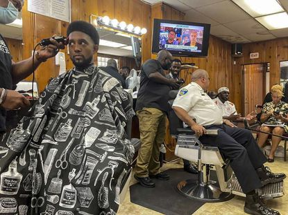 Crime reduction strategies are discussed at the barbershop level as Mayor Brandon Scott gets a touchup at Antonio's hair design in Brooklyn with Baltimore Police Commissioner Michael Harrison last Friday. (Justin Fenton/Baltimore Sun).