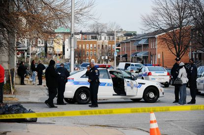 Baltimore City Police officers investigate a shooting scene at 2500 block of Woodbrook Avenue.