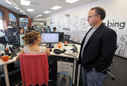 Baltimore, Md.--5/8/15-- Kevin Buerger, right, executive VP of Jellyfish, a UK based internet marketing company, italks with Kelly Pollhammer, left, at the company's US headquarter in Baltimore. The company has grown from a one man shop to over 60 employees and $100 million in revenue. Kenneth K. Lam/Baltimore Sun DSC_4419 bz-jellyfish-p4-marketing lam