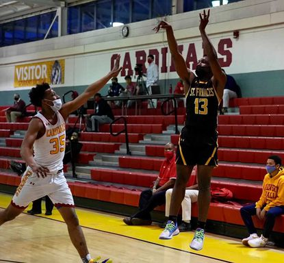 St. Frances guard Byron Ireland shoots a 3-pointer over Calvert Hall guard Mike Williams during a Monday night matchup at the Towson campus.