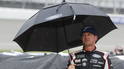 NASCAR driver Clint Bowyer stands on pit row while waiting out a rain delay at Michigan International Speedway on June 9. The postponed race will be run on June 10.