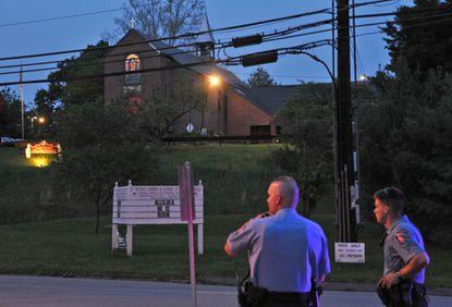 Officers are posted Thursday evening on Rogers Avenue in Ellicott City, near St. Peter's Episcopal Church. Three people were shot -- two fatally -- in and around the church.