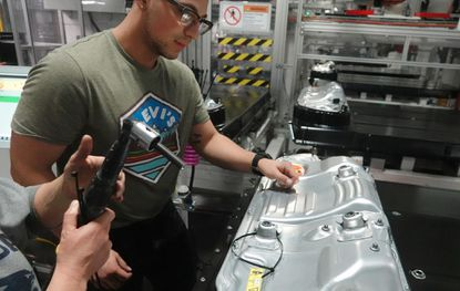 In this Dec. 3, 2018, file photo, workers put the finishing touches on a battery pack for a Tesla Model 3 sedan at Tesla's northern Nevada Gigafactory in Reno, Nev. Tesla says a fire in one of its cars in Shanghai was caused by the failure of a single battery module and investigators found no defects in the car's systems. (Benjamin Spillman/The Reno Gazette-Journal via AP, File)