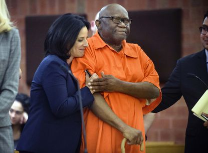 In this June 8, 2017 file photo, Innocence Project lawyer Vanessa Potkin, left, hugs Alfred Swinton, in Superior Court in Hartford, Conn. Swinton served almost two decades in prison for the 1991 killing of Carla Terry before he was cleared based on new DNA evidence. Several states have moved to toughen regulations on the use of jailhouse informants.