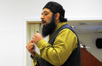Iman Omar Baloch, of the Masjid Al Falaah mosque in Abingdon, gives a brief lecture on Islam Saturday during a community iftar dinner as the congregation observes the Muslim holy month of Ramadan.