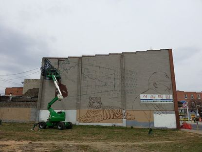 Artists have started a mural near Charles Street and North Avenue in Station North.