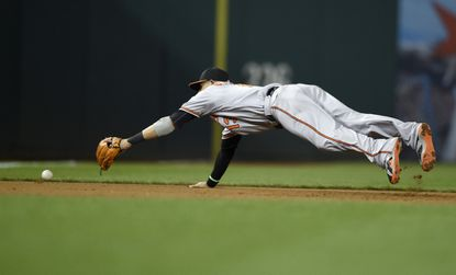 Baltimore Orioles third baseman Manny Machado (13) dives for a ball hit by Washington Nationals' Wilson Ramos that went for a double during the fifth inning of an interleague baseball game, Wednesday, Sept. 23, 2015, in Washington.