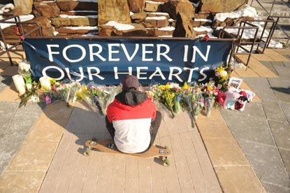 Tyler Bohn of Mt. Airy, a former employee of Zumiez, and good friend of Brianna Benlolo, sits on his longboard thinking about her in front of a memorial life in her memory at the Mall in Columbia on Monday, Jan 27. Benlolo, one of the two shooting victims, inspired Bohn to start longboarding.