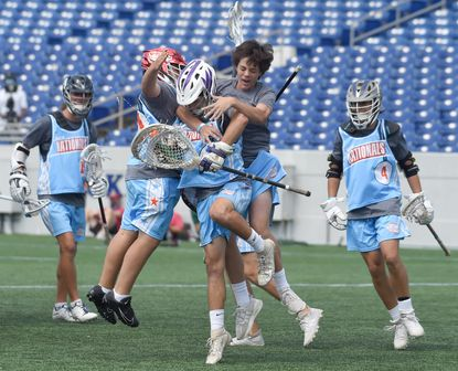 Madlax Nationals teammates celebrate their win over the Annapolis Hawks during a Naptown Challenge lacrosse tournament game at Navy-Marine Corps Memorial Stadium in Annapolis on Tuesday, August 5.