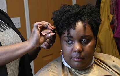 Yasmine Young, owner and stylist, Diaspora Salon, finishes styling Sabrina Bullock's hair. The Baltimore City Council is looking to join a growing wave of cities and states in prohibiting discrimination based on hair texture and style.