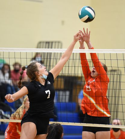 Patterson Mill's Ella Laurentius puts the ball over the net with Fallston's Amanda Sharpe leaping to try for the block during the girls volleyball game at Patterson Mill Tuesday October 12, 2021.