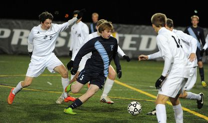 Chesapeake's Ryan Gruss dribbles the ball in the second half surrounded by Walt Whitman players.
