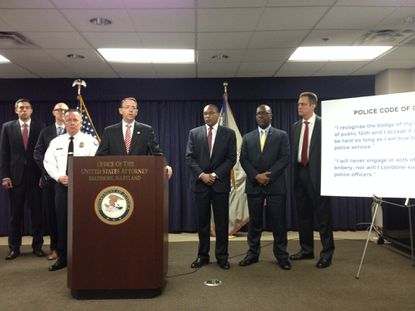 U.S. Attorney Rod Rosenstein, flanked by police, DEA and FBI officials, announces the take-down of sixBaltimore detectives and a sergeant.