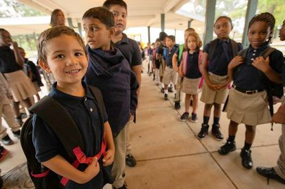 First-grader Anthony Davila, 6, joins the line of Laurel Elementary students outside the former Greenbelt Middle School Tuesday, Sept. 4, after students were bused to Greenbelt from Laurel Elementary, which is closed due to on-going construction work.