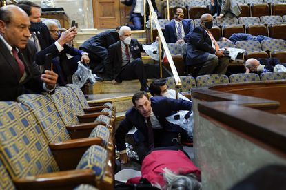 In this Jan. 6, 2021, file photo, people shelter in the U.S. House of Representatives chamber as rioters try to break in at the U.S. Capitol in Washington, D.C. (AP Photo/Andrew Harnik, File)