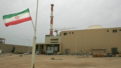 A file photo taken on April 03, 2007 shows an Iranian flag fluttering outside the building housing the reactor of the Bushehr nuclear power plant in the Iranian port town of Bushehr. (Photo by Behrouz MEHRI / AFP)B