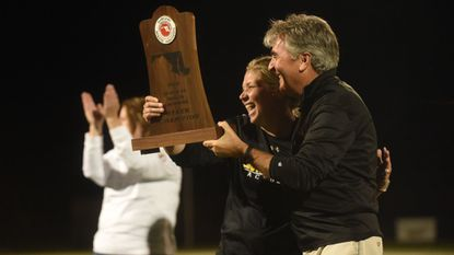 South Carroll head coach Brigid Scanlon, accepts the championship trophy from athletic director Jim Horn after the team's win over Hereford during the Class 2A girls lacrosse state championship game at Paint Branch High School on Tuesday, May 21.