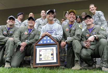 Baltimore Ravens head coach John Harbaugh has his picture taken with members of the military after being given a flag that was flown over Afghanistan on a military mission
