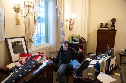 TOPSHOT - Richard Barnett, a supporter of US President Donald Trump sits inside the office of US Speaker of the House Nancy Pelosi as he protest inside the US Capitol in Washington, DC, January 6, 2021. - Demonstrators breeched security and entered the Capitol as Congress debated the a 2020 presidential election Electoral Vote Certification. (Photo by SAUL LOEB / AFP) (Photo by SAUL LOEB/AFP via Getty Images)