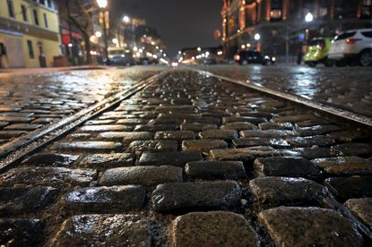 Cobblestones glisten on Thames Street at the end of Broadway in a view at Fells Point last year. (Karl Merton Ferron/Baltimore Sun).