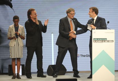 """From left to right, goodwill ambassador of the ONG """"Grandir Ensemble"""" Amanda Dushime, U2 singer Bono, Philanthropist Philanthropist and Co-Chairman of the Bill & Melinda Gates Foundation Bill Gates and France's President Emmanuel Macron congratulate each other on stage during the Global Fund to Fight AIDS event at the Lyon's congress hall, central France, Thursday, Oct. 10, 2019. French President Emmanuel Macron said the conference of the Global Fund to fight against AIDS, tuberculosis and malaria raised at least $13.92 billion for the next three years. (AP Photo/Laurent Cipriani)"""