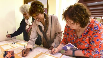 From left, Vivian Jones-Samuels, Norma Woods and Maria Rytkola, members of Christ Lutheran Church, take turns signing some of the 400 Mother's Day cards which will be sent to immigrant women from Central America, either newly arrived or being held in a detention center.