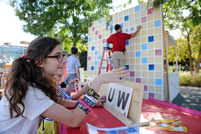 """Kathryn Jagelka discusses strategy with an opponent during a game of """"Words With Strangers"""" at the Baltimore Book Festival."""