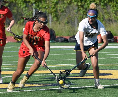 Dulaney #10, Sammy White and Catonsville #12, Marisa Massimini, battle for possion of the ball in the 1st half. Catonsville hosts Dulaney in girls lacrosse Tuesday May 18, 2021 at Catonsville High School.