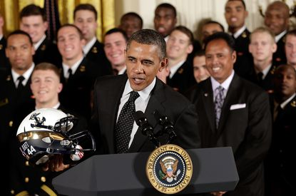 President Barack Obama shows off the Navy football helment given to him after he presented the Commander-in-Chief's Trophy to the Midshipmen at the White House.