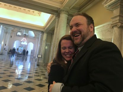 Del. Luke Clippinger, right, gets a congratulatory hug from Melissa Broome of the Job Opportunities Task Force, who has been lobbying for the paid sick leave bill.
