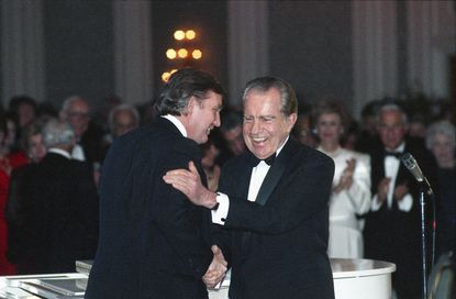 In this March 11, 1989, photo Donald Trump shakes hands with former President Richard Nixon at a tribute gala to Nellie Connally at the Westin Galleria ballroom in Houston, Texas.