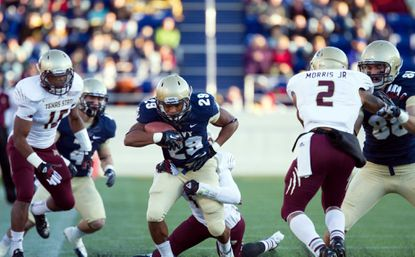 Navy running back Geoffrey Whiteside, center, runs the ball up the middle as Texas State cornerback Darryl Morris, right, looks to make the tackle in the first half.